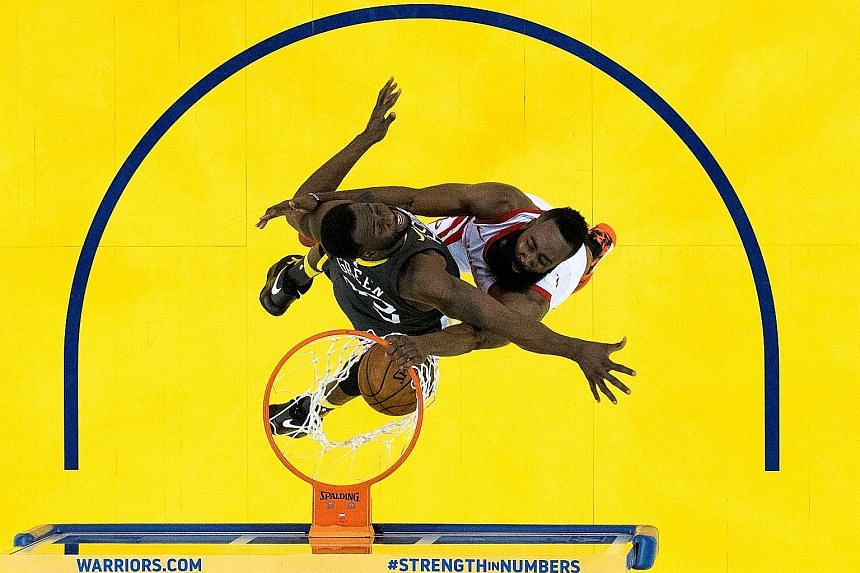 Houston guard James Harden dunking the ball as Golden State forward Draymond Green fails to stop him in Game 4 of the Western Conference Finals at the Oracle Arena in Oakland, California.