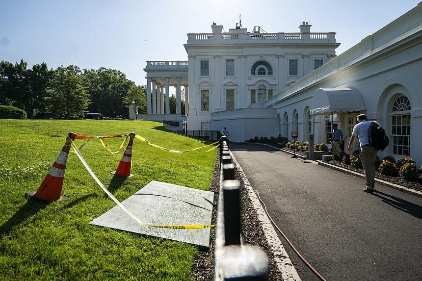 A wooden board yesterday covering a sinkhole in the North Lawn of the White House, just outside the press briefing room.