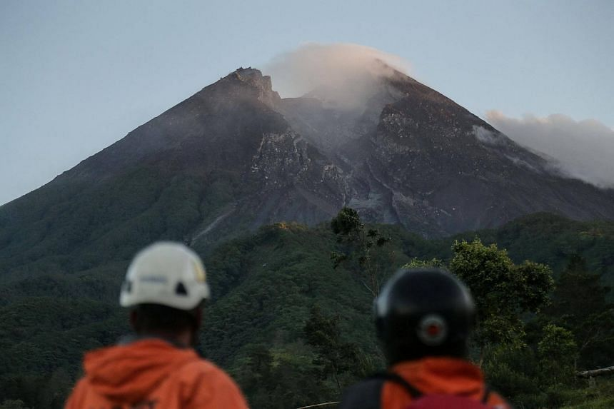 Members of a search and rescue team watch the volcano activity on Mount Merapi after its alert level was increased following a series of minor eruptions in Cangkringan, Yogyakarta, Indonesia, on May 22, 2018.