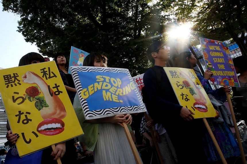 Protesters hold placards during a rally against harassment at Shinjuku shopping and amusement district in Tokyo, on April 28, 2018.