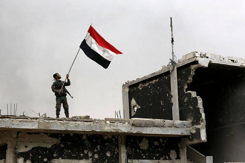 File photo showing a member of the Syrian pro-government forces raising the national flag atop a damaged building on the southern outskirts of Damascus on May 22, 2018.