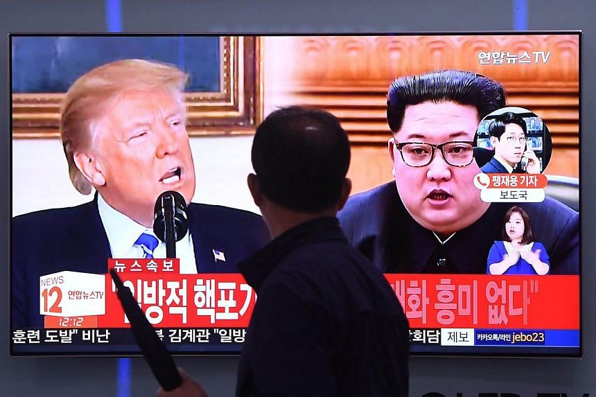 A man walks past a television news screen showing North Korean leader Kim Jong Un (right) and US President Donald Trump at a railway station in Seoul on May 16, 2018.