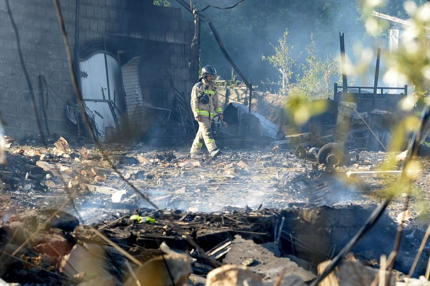 A fire-fighter inspects the area affected by the explosion of a fireworks storehouse in Tui.
