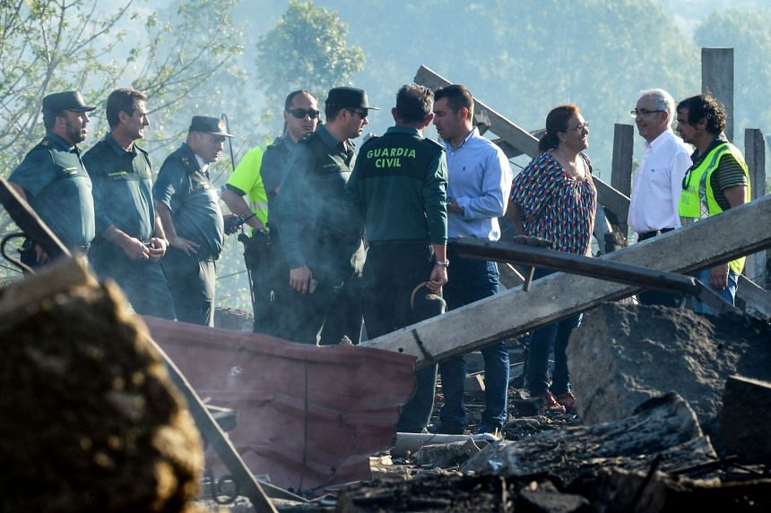 Civil guards gather at the area affected by the explosion of a fireworks storehouse in Tui.