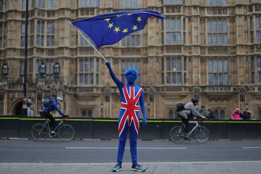An anti-Brexit protester dressed in a suit bearing the British flag and waving an EU flag stands outside the Houses of Parliament in London.