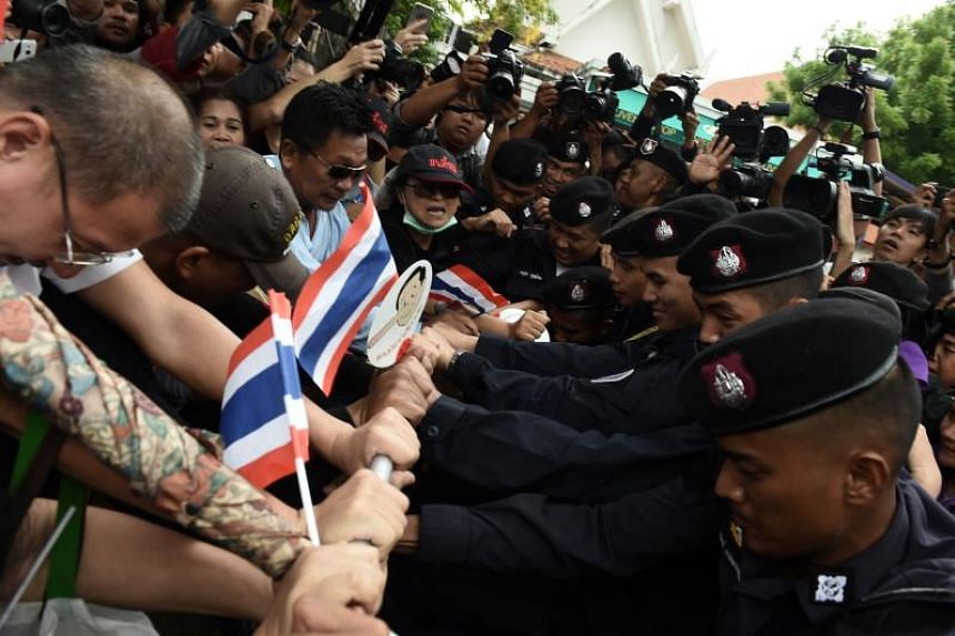 Demonstrators attempt to break through a phalanx of police outside Thammasat University during a protest to mark the fourth year of junta rule in Bangkok, Thailand, on May 22, 2018.