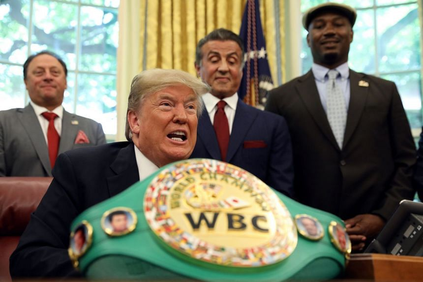 With Sylvester Stallone (second right) and Lennox Lewis (right) behind him, Trump speaks before signing the pardon.