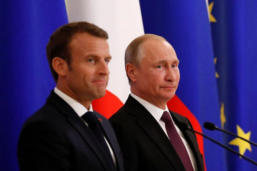 Putin (right) and Macron attend a signing ceremony after talks in St Petersburg, Russia.
