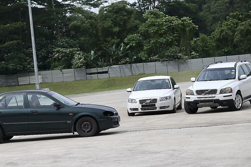 "Left: ST journalist Charmaine Ng, assuming the role of a VIP in this simulation exercise, being whisked away to a getaway car by Police Security Command officers after the four-car VIP convoy was ""attacked"" by gunfire. Right: Police SecCom officers ("