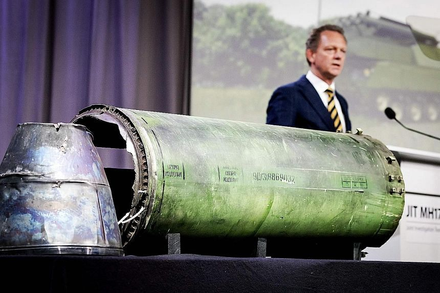 Dutch prosecutor Fred Westerbeke speaks next to a part of the Buk rocket fired at MH17 over Ukraine, during the press conference in Bunnik, Holland, yesterday.