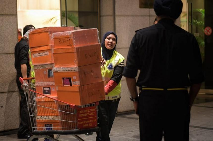 Boxes containing a large number of luxury handbags as well as bags filled with jewellery, cash, watches and other valuables were carted away during police raids on former Malaysian prime minister Najib Razak's home and condo units linked to his fam