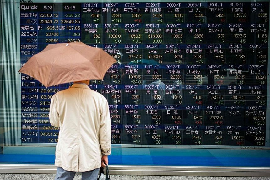 A man stands next to a stock indicator showing stock prices of Japanese companies listed on the Tokyo Stock Exchange on May 23, 2018.