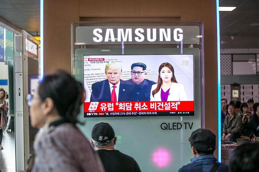 People watch a television screen broadcasting a news report, featuring images of US President Donald Trump and North Korean leader Kim Jong Un, in Seoul.
