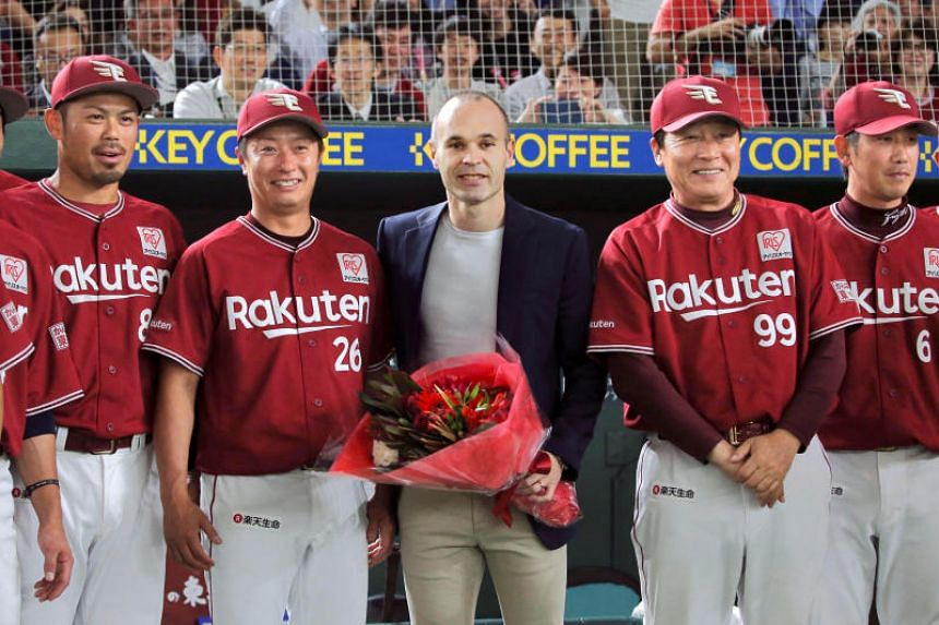 Spain midfielder Andres Iniesta (centre) poses with Japan's professional baseball team Tohoku Rakuten Golden Eagles manager Masataka Nashida and players at the Tokyo Dome in Tokyo, on May 24, 2018.