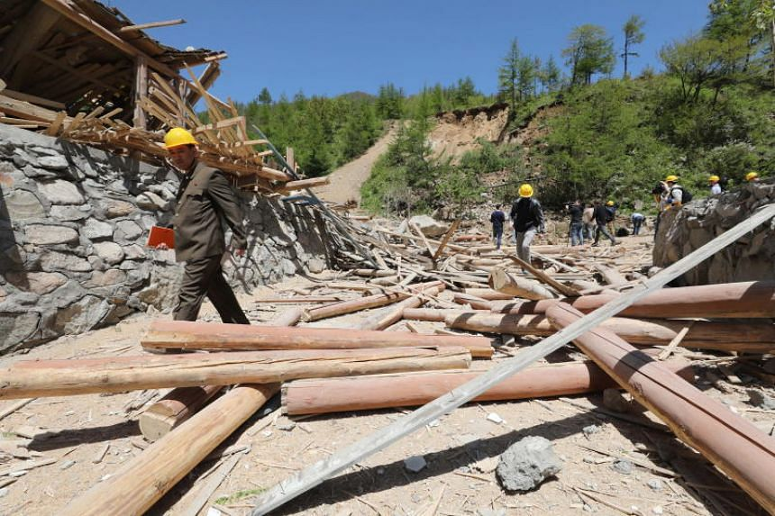 People inspect the ruins of a structure in the aftermath of an explosion at an entrance tunnel during the first day of dismantling at North Korea's Punggye-ri nuclear test site on May 24, 2018.