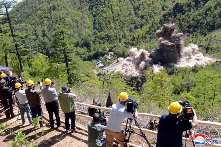 Members of the international media witnessing an explosion at an entrance tunnel during the first day of dismantling at North Korea's Punggye-ri nuclear test site on May 24, 2018.