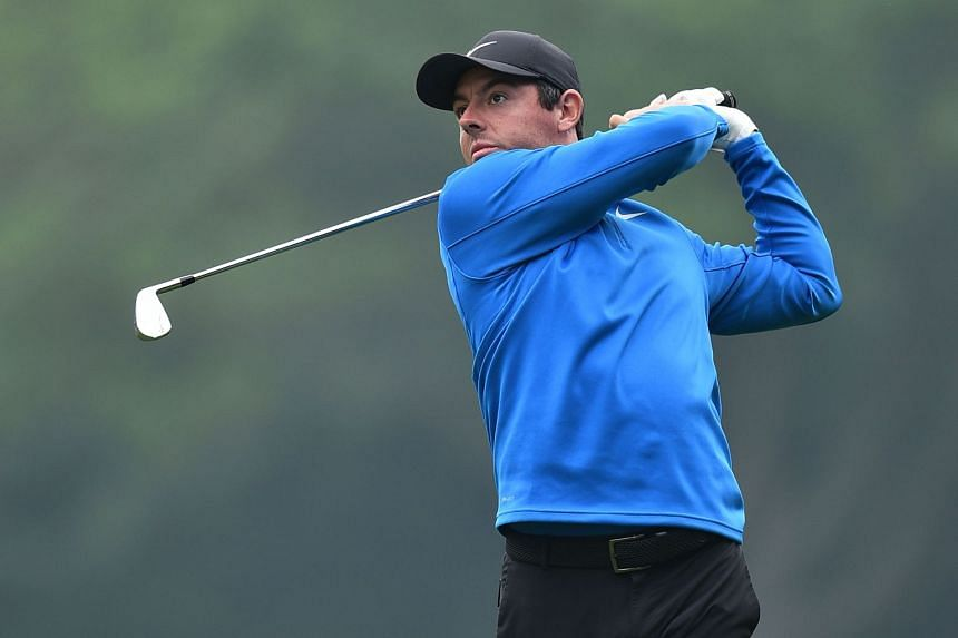 McIlroy watches his iron from the 18th fairway during his first round 67.