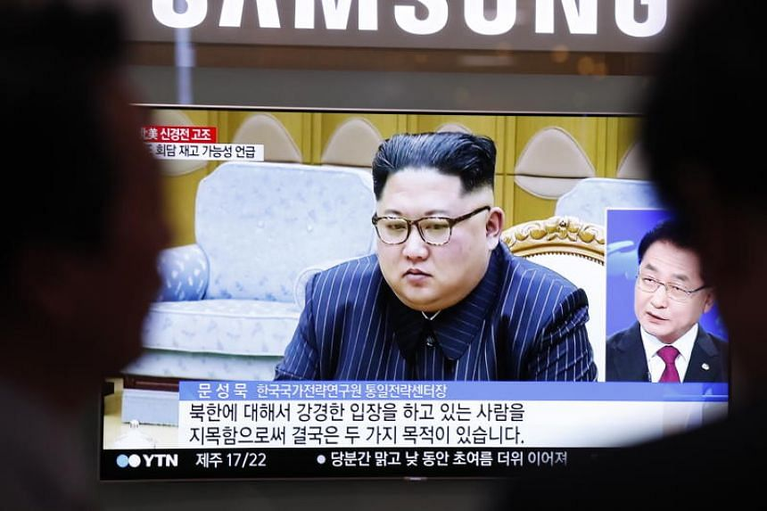 South Koreans watch a television news broadcast, showing North Korean leader Kim Jong Un, in Seoul on May 24, 2018.