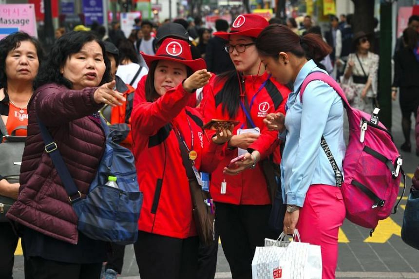 South Korean tourist information helpers (in red) guide Chinese tourists in the popular Myeongdong shopping district in Seoul, on April 25, 2017.
