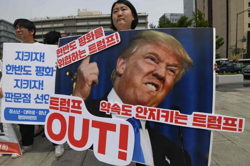 A protester holds a placard showing a picture of US President Donald Trump during an anti-Trump rally near the US embassy in Seoul on May 25, 2018.