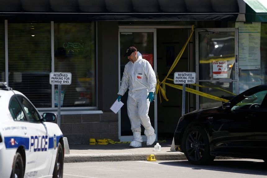 A police forensic investigator surveys the scene at the Bombay Bhel restaurant.