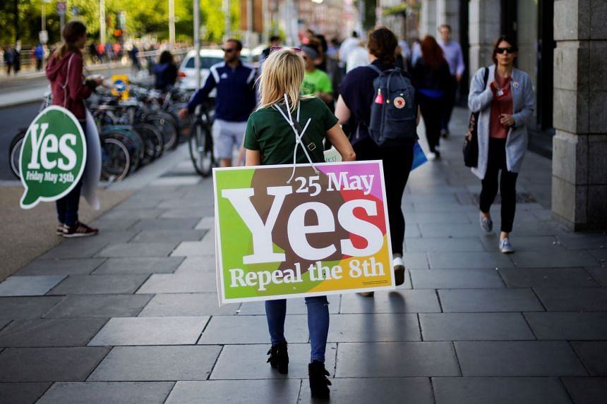 A woman carries a placard as Ireland holds a referendum on liberalising abortion laws, in Dublin, Ireland.
