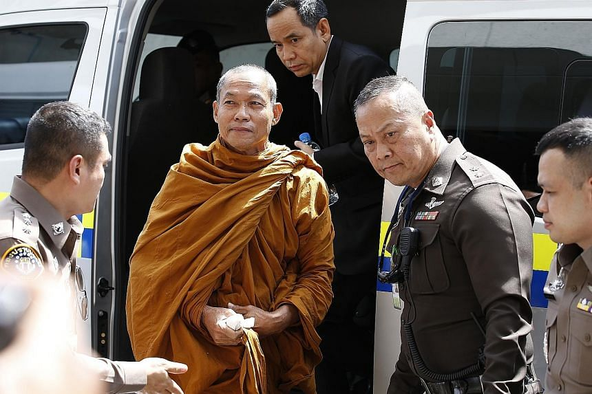Thai Buddhist monk Luang Pu Buddha Issara being escorted by police officers at the criminal court in Bangkok on Thursday. He was charged over the sale of amulets with fake royal seals and has been defrocked, said Thai police.