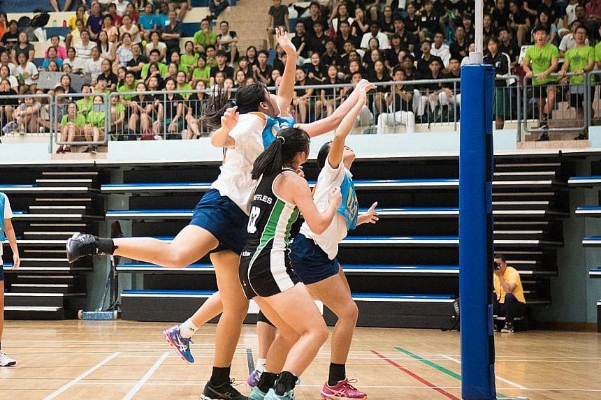 ACJC (in blue and white) on the attack against RI with goal shooter Syntyche Yeo (third from right) and goal attack Kaylee Lim. They won 38-34 for their first A Division netball title since 2013.