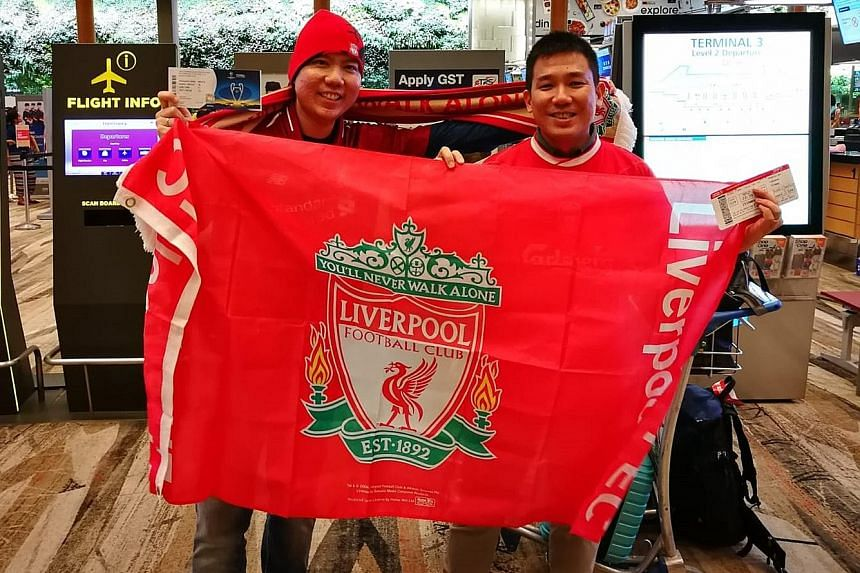 Singaporeans Wesley Wee (left) and Wai Chung Tai proudly displaying a Liverpool flag at Changi Airport last night before flying off to Kiev to support Liverpool in their Champions League final against Real Madrid tonight.
