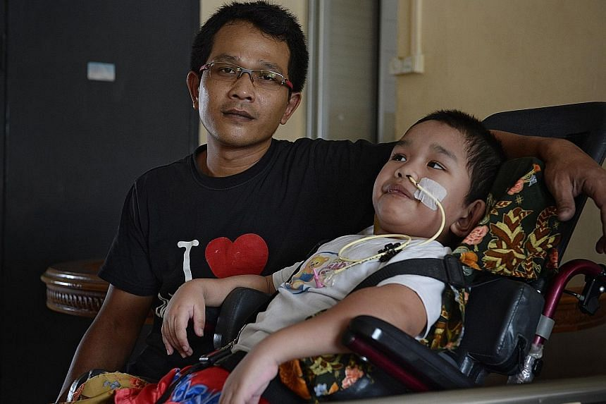 Mr Abdul Halim Abdul Aziz with his son Syahriz Matin in a 2016 photo. Syahriz was found submerged face downwards in the wave pool of the Civil Service Club's Bukit Batok swimming facility on Oct 11, 2015, and suffered traumatic brain injury. Now 10,