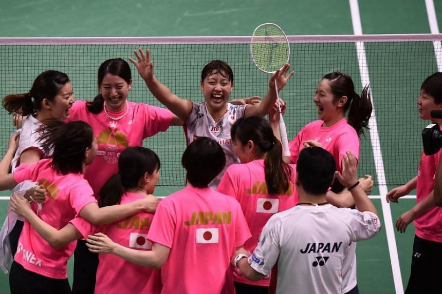 Japan's Nozomi Okuhara (centre) celebrates with teammates after defeating Thailand's Nitchaon Jindapol during their women's singles final match at the  Uber Cup in Bangkok on May 26, 2018.