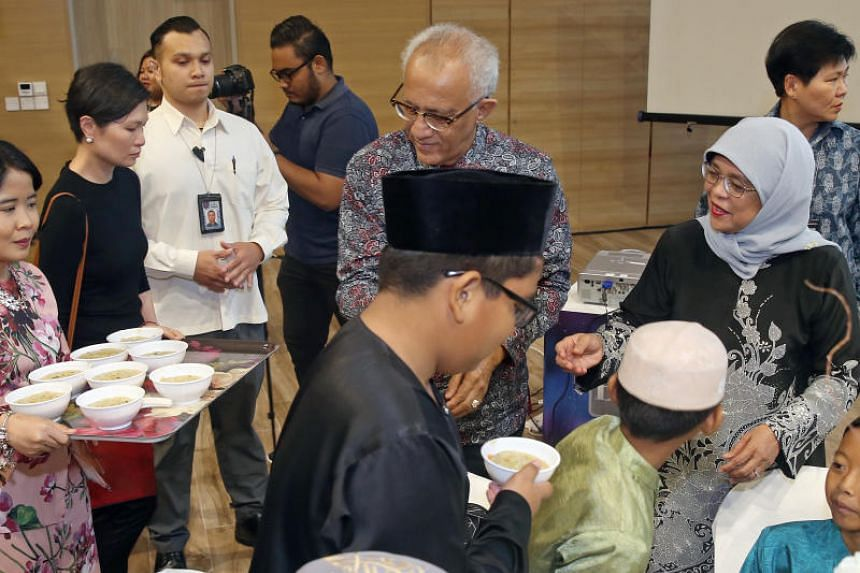 President Halimah Yacob and her husband Mr Mohamed Abdullah Alhabshee serve porridge to beneficiaries during a Ramadan charity iftar on May 26, 2018.