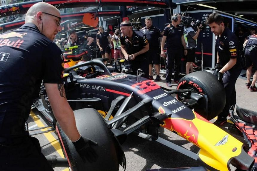 Mechanics work on the car of Red Bull's Max Verstappen after a crash during the third practice session for the Monaco Grand Prix on May 26, 2018.