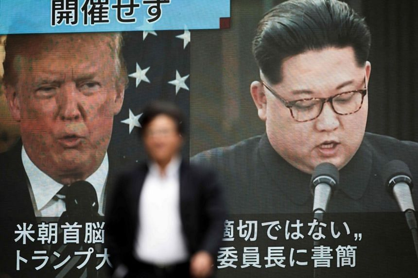 A pedestrian in Tokyo walks in front of a screen flashing a news report relating to US President Donald Trump cancelling his meeting with North Korean leader Kim Jong Un, on May 25, 2018.