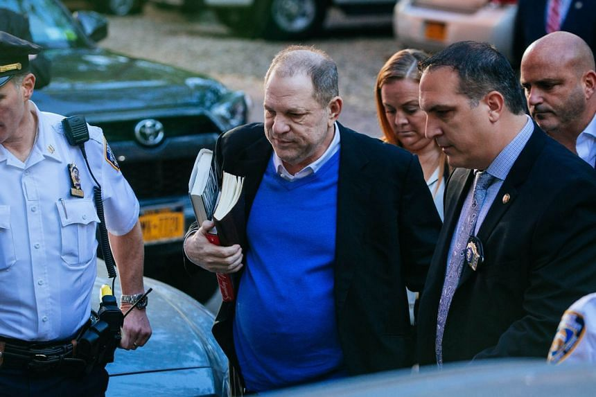 Weinstein turns himself in to police in New York after being served with criminal charges.