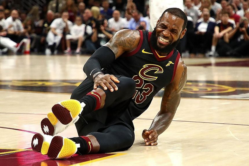 LeBron James of the Cleveland Cavaliers played a pivotal role in his side's 109-99 win against the Boston Celtics on Friday, despite a moment (above) when he went down, clutching his knee in pain.