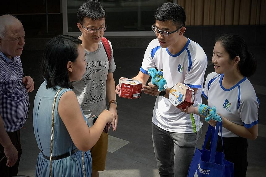 China Taiping Insurance Singapore staff selling fortune cookies and elephant plushies at Chinatown Point yesterday to help raise funds for The Straits Times School Pocket Money Fund. The street sales will continue today.