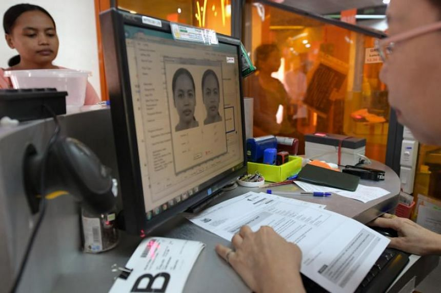 A new maid having her thumbprint taken during registration for her work permit at the Ministry of Manpower Services Centre.