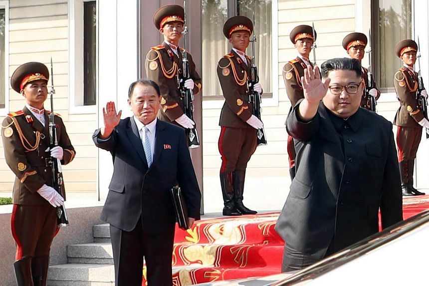 North Korean leader Kim Jong Un (right) waves to South Korean President Moon Jae In as they bid farewell after their summit at the truce village of Panmunjom, North Korea, on May 26, 2018.