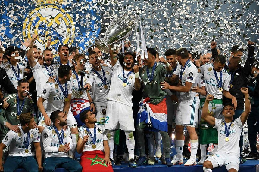 Real Madrid's Brazilian defender Marcelo lifts the trophy as Real Madrid players celebrate winning the Uefa Champions League final football match on May 26, 2018.