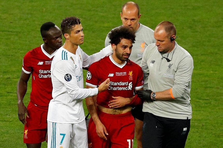 Liverpool's Mohamed Salah (centre) with Sadio Mane (left) and Real Madrid's Cristiano Ronaldo as he is substituted after sustaining an injury during the Uefa Champions League final football match on May 26, 2018.