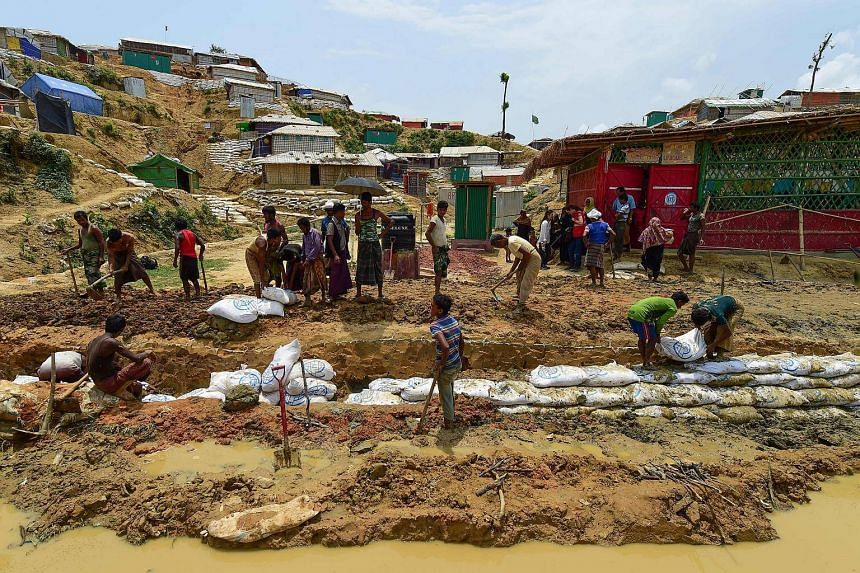 Rohingya refugees make a drainage canal in preparation for the upcoming monsoon season in Kutupalong refugee camp in Ukhia, on May 8, 2018.
