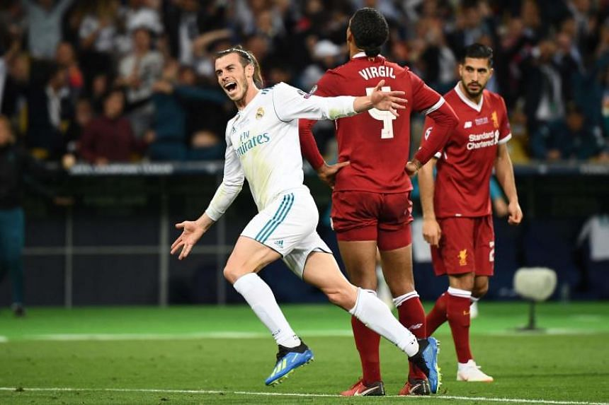 Real Madrid's Welsh forward Gareth Bale (left) reacts after scoring his team's third goal during the UEFA Champions League final football match between Liverpool and Real Madrid at the Olympic Stadium in Kiev, Ukraine, on May 26, 2018.