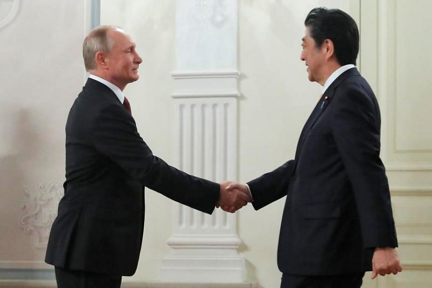 Russian President Vladimir Putin (left) shakes hands with Japanese Prime Minister Shinzo Abe before the opening ceremony of the cross-cultural year of Russia and Japan at the Bolshoi Theatre in Moscow, on May 26, 2018.
