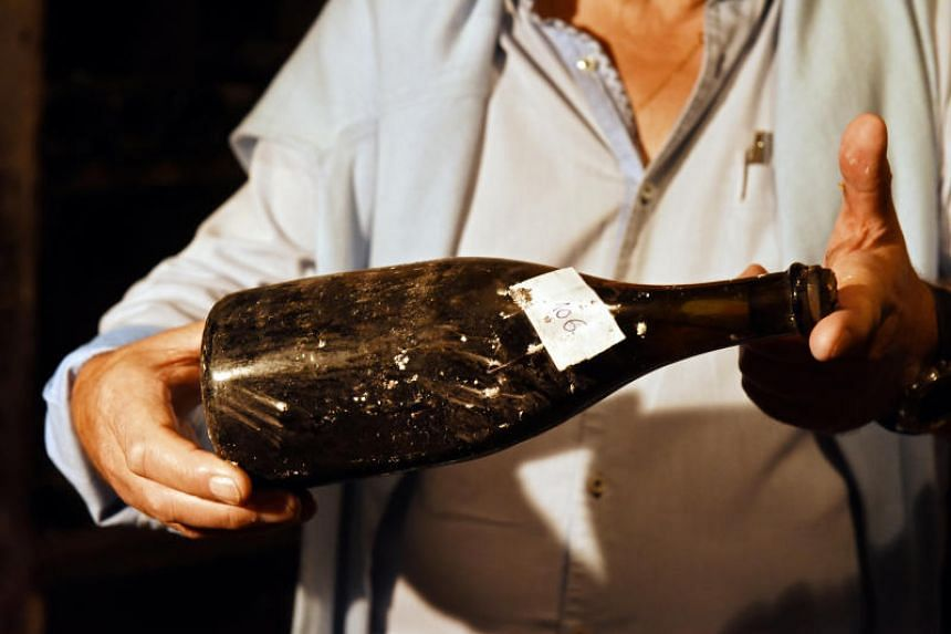 """One of three bottles of vin jaune """"yellow wine"""" from 1774, is presented in a cellar in Arbois, France, on May 22, 2018."""