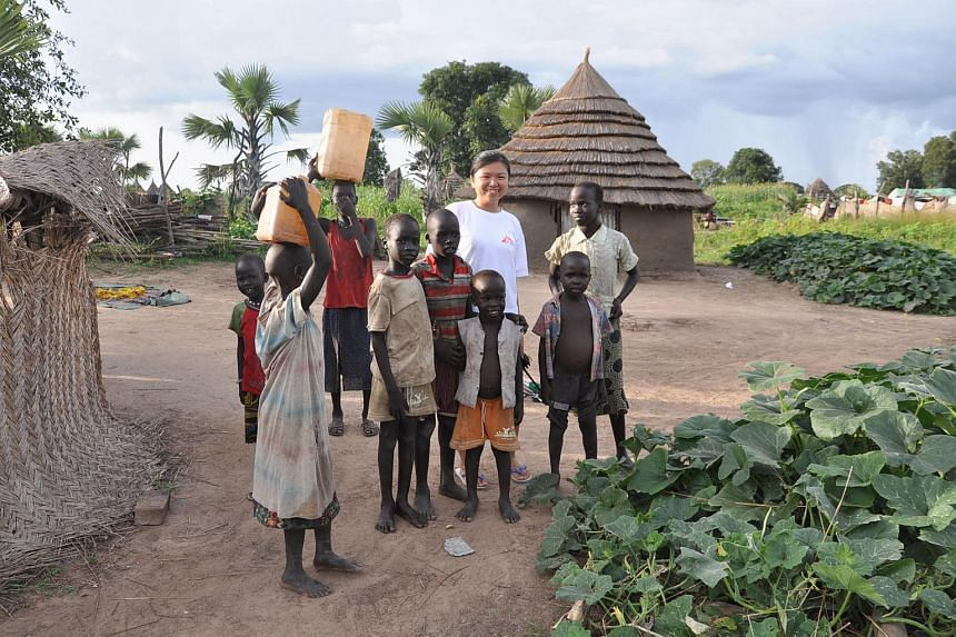Miss Lim Suet Fong with a group of village children in Pibor in South Sudan.