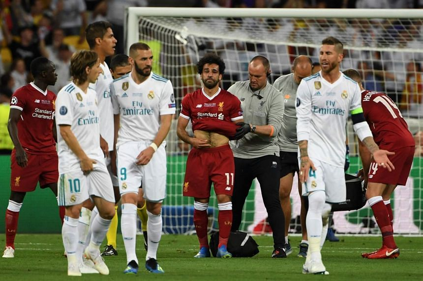 Liverpool's Egyptian forward Mohamed Salah is led off the pitch after hurting his shoulder in a challenge with Real Madrid's Spanish defender Sergio Ramos (right) during the Uefa Champions League final in Kiev, Ukraine on May 26, 2018.