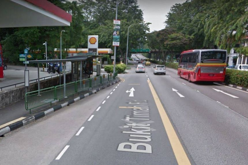 A bus stop along Bukit Timah Road with railings situated in front of it.