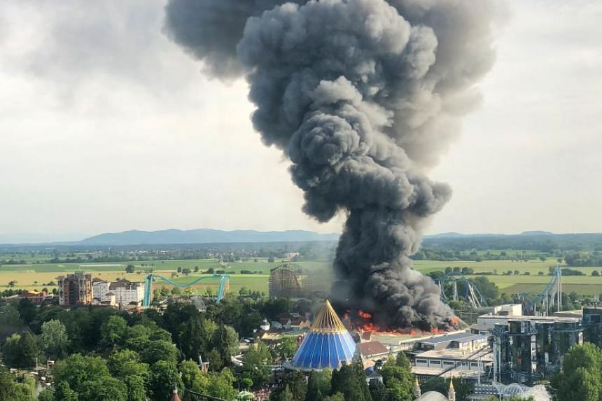 A black column of smoke can be seen rising from a fire in a warehouse in Europa-Park in Rust, southern Germany, on May 26, 2018.