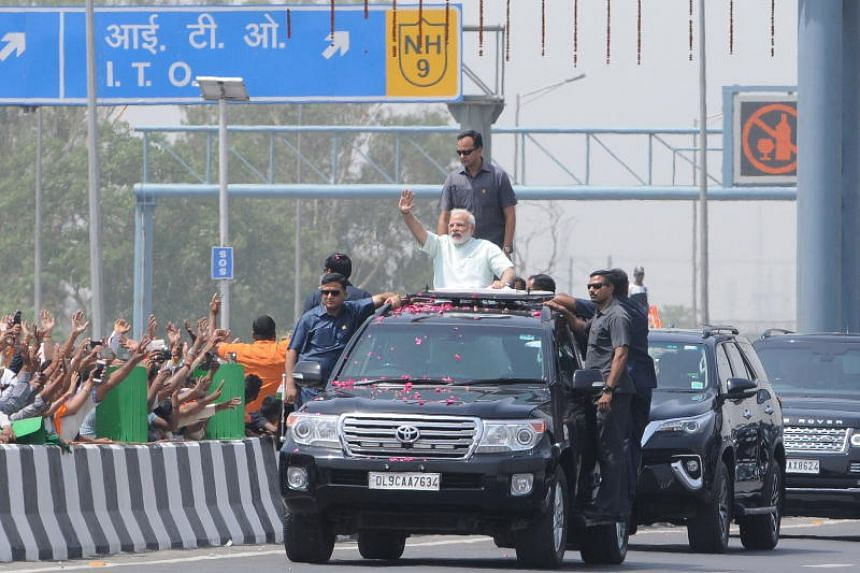 Indian PM Narendra Modi (in white) waving to the crowd during a roadshow after inaugurating the first phase of the Delhi-Meerut Expressway in New Delhi on May 27, 2018.
